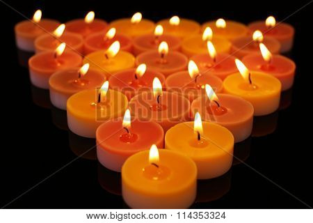 Many burning small candles on dark background, close-up