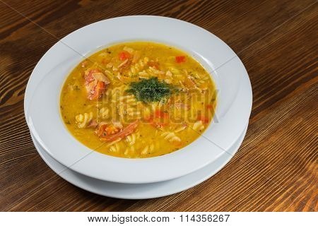 Soup with vegetables and herbs in the white plate.