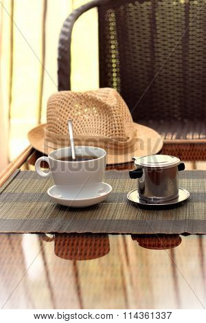 Morning Coffee Served In Vietnam Coffee Filter On Rattan Table With A Hat On Table