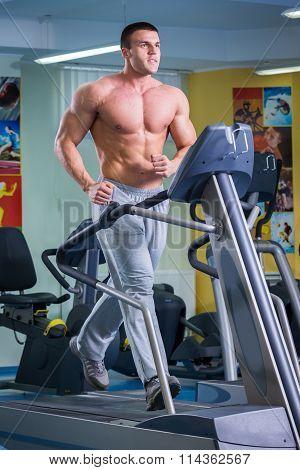 A man runs on a treadmill. bodybuilder in the gym.