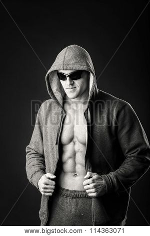 An athlete in a sports jacket with a hood on a dark background. A man shows his muscles revealing jacket. Photos for sporting magazines, posters and websites.