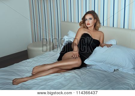 Beautiful Girl With Long Legs Lying On The Bed.