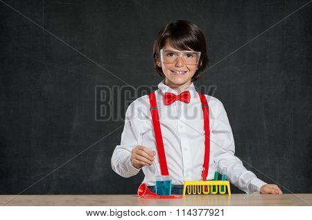 Smiling little boy doing an experiment. Young boy wearing protective glasses and playing with flasks for chemistry. Cheerful child doing an experiment with testtube isolated on blackboard.
