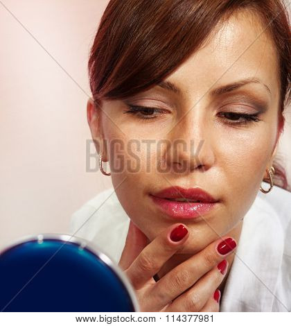 beautiful face smartens up in front of compact mirror