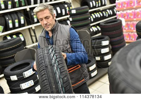 Mechanic taking new tire for workshop