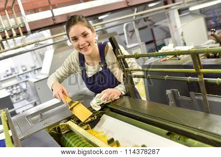 Woman in printshop preparing machine