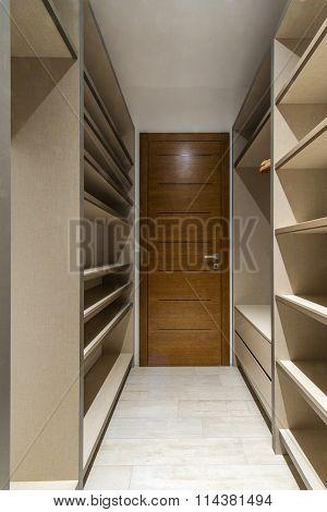 Big wooden wardrobe interior in modern home