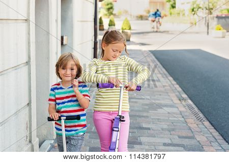 Two cute kids playing outdoors, riding scooters