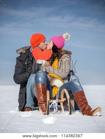 kissing partners on sledge in wintertime landscape