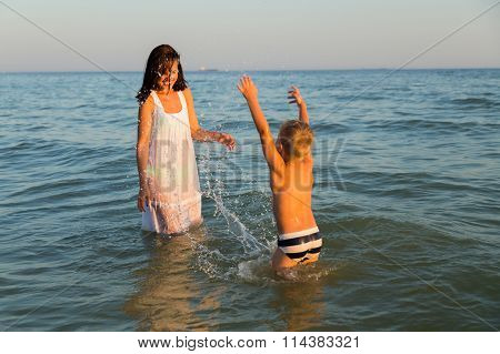 Young mother with son playing in the sea