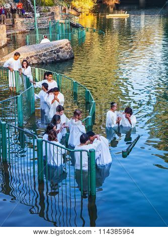 YARDENIT, ISRAEL - JANUARY 21, 2012: Christian pilgrims baptized in the Jordan River. They enter the water, dressed in white shirt