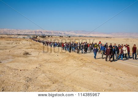 THE BORDER WITH JORDAN, ISRAEL - JANUARY 18, 2008: The Procession.  Pilgrims and tourists walk through the desert after visiting the site of the Baptism of Jesus in the Jordan River