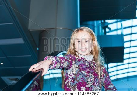Cute little child in shopping center standing on escalator