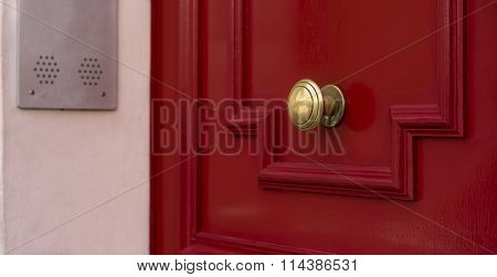 Shiny Brass Doorknob On Red Wooden Door