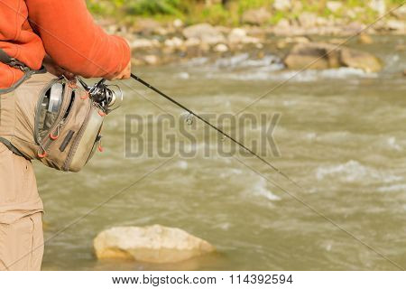 Fishing in the mountain river in summer.