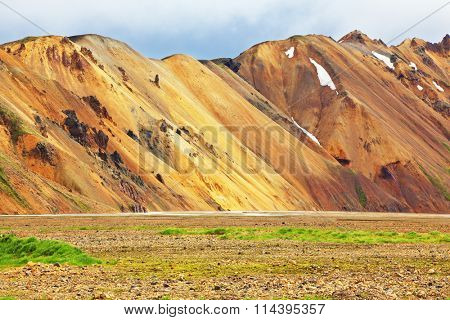 Smooth orange rhyolite mountains in Landmannalaugar nature reserve. In the hollows snow left over from last year
