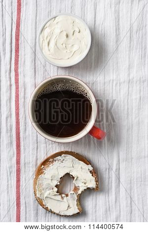A bagel with cream cheese and a bite taken out. on a towel with cup of coffee and crock filled with cream cheese. Vertical format with copy space.