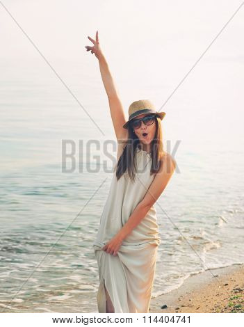 Joyful casual girl walking on a sea beach and happy screaming with hand up.