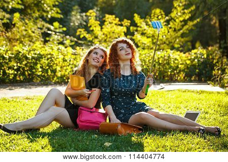Two Girls Make Selfie Sitting On The Lawn.