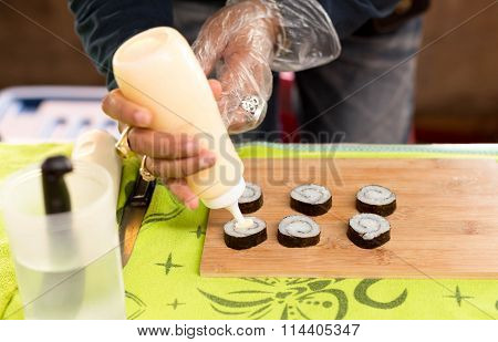Home Make Shushi Putting Cream Sauce On Sushi Rolls