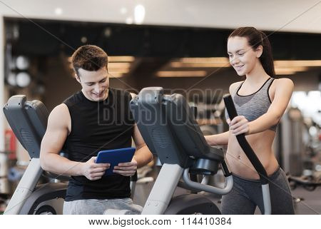woman with trainer exercising on stepper in gym