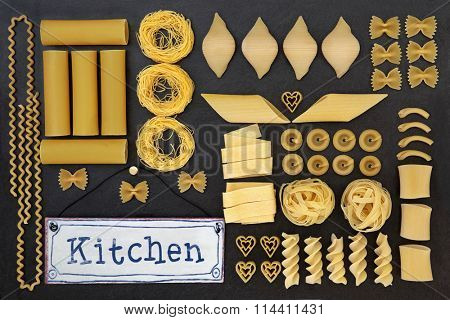 Dried italian pasta food selection with old metal kitchen sign forming an abstract background over slate.