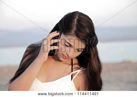 Beautiful young european female teenager with long dark hair on a mobile phone.