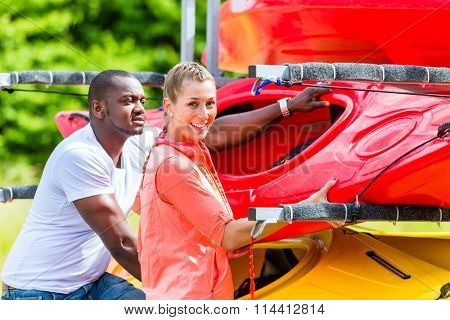 Man and woman getting boat from car trailer