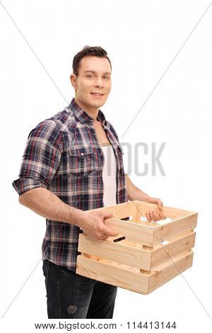 Vertical shot of a young guy holding an empty wooden crate and looking at the camera isolated on white background