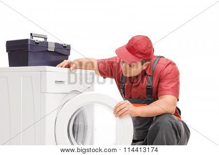 Young male plumber in a gray jumpsuit looking at a washing machine isolated on white background