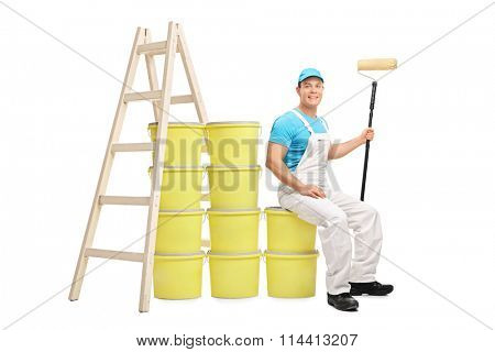 Young male decorator sitting on a pile of color buckets next to a wooden ladder isolated on white background