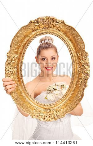 Vertical shot of a cheerful bride posing behind a vintage picture frame isolated on white background
