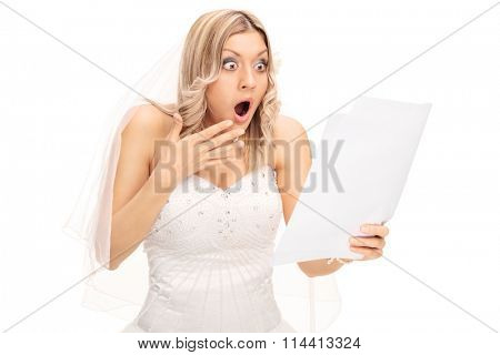 Shocked blond bride looking at a piece of paper in disbelief isolated on white background