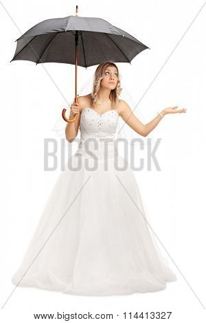 Full length portrait of a young bride in a white wedding dress holding an umbrella isolated on white background