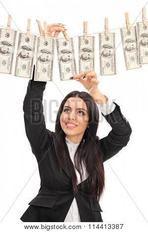 Vertical shot of a young businesswoman pinning money on a clothesline isolated on white background