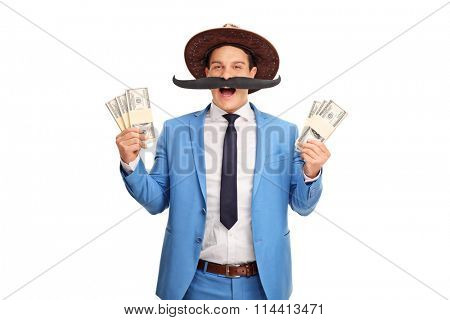 Young man with a fake moustache and a cowboy hat holding few stacks of money isolated on white background