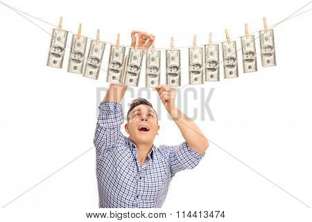 Studio shot of a happy young man pinning money on a clothesline and drying them isolated on white background