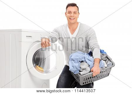 Content young man holding a laundry basket and standing next to a washing machine isolated on white background