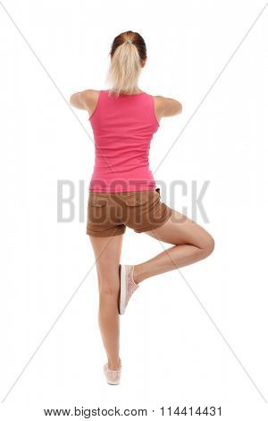 Back view of girl standing in front of a warm up exercise.  Rear view people collection.  backside view of person.  Isolated over white background. girl meditates standing on one leg.