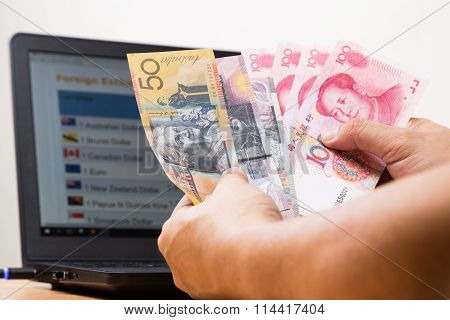 Hand Sorting Australian Dollar And China Yuan With Computer Background