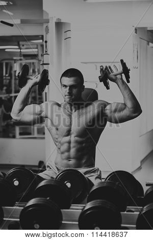 Muscular man in the gym. Work on the arm muscles. Training on a simulator. Exhausting work on his body.
