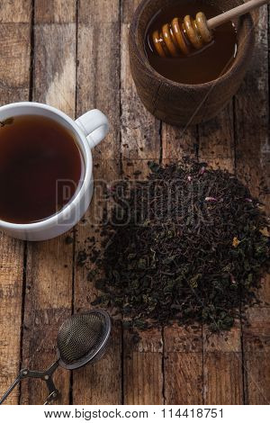The cup of tea and honey on a wooden table