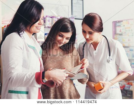 Two Doctors Showing Products In Catalog To Client