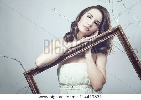 Romantic Woman Holding A Picture Frame On Tree Background