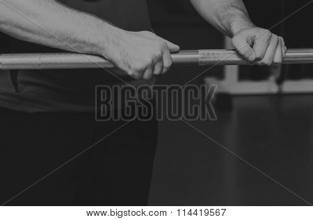 Girl's hand on the barbell. Beautiful girl goes in for sports in the gym.