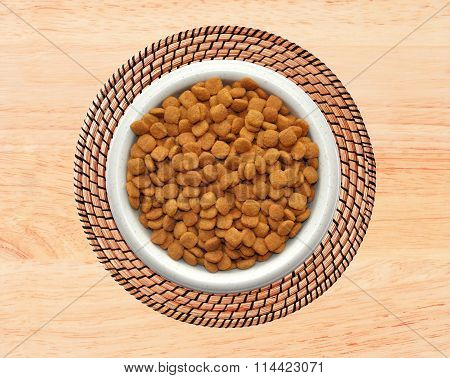 Dry Cat Food In Plate On Wicker Placemat On Wooden Background