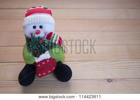 Plush Toy In The Form Of A Snowman On A Wooden Board