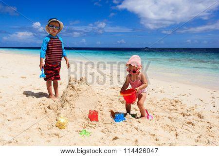 little boy and girl building sandcastle on beach