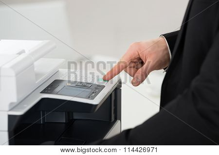 Businessman Operating Printer In Office