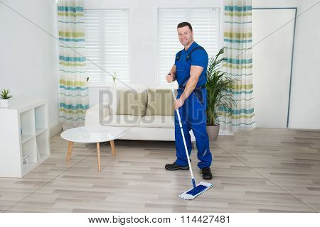 Smiling Worker Cleaning Floor With Mop At Home
